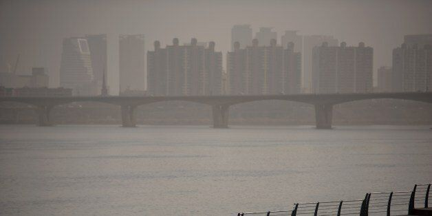 A man takes a selfie as he stands before the Han River and the Seoul city skyline during heavily polluted...