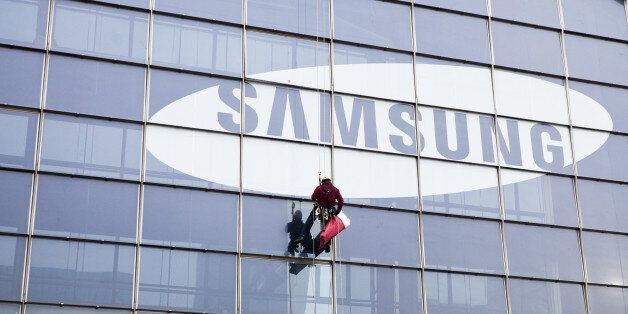 Paris, France - January 20, 2012: A window cleaner coming down from a tall skyscraper with the Samsung...