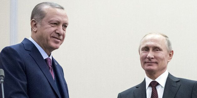 Russia's President Vladimir Putin (R) shakes hands with Turkey's President Tayyip Erdogan during a meeting...