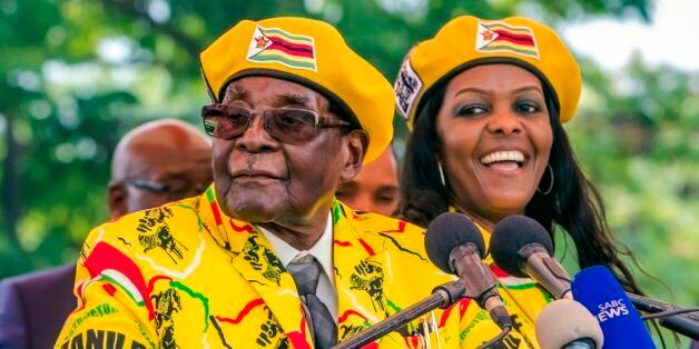 Zimbabwe's President Robert Mugabe (L) addresses party members and supporters gathered at his party headquarters...