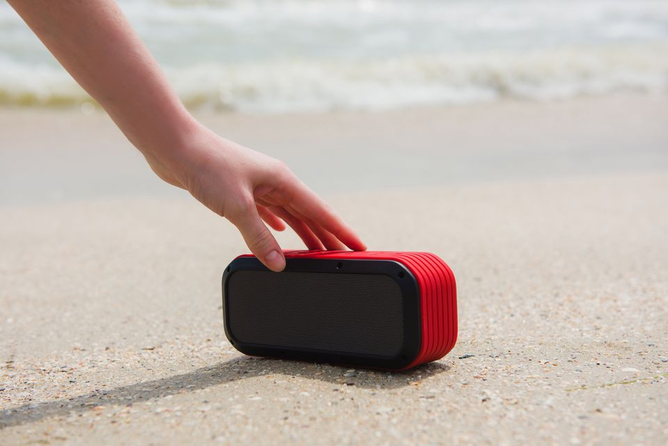 Female hand touch portable speaker. Woman and usb wireless acoustic at beach with