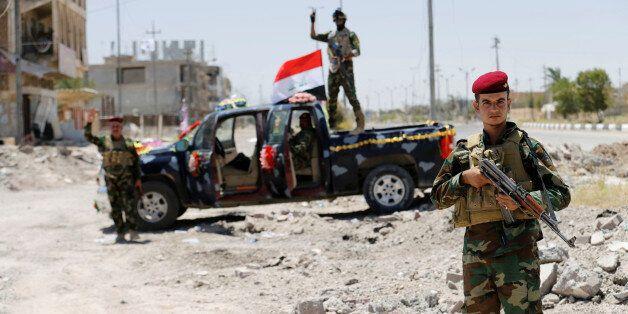 *자료사진: Iraqi government forces react to the camera in Falluja after government forces recaptured the...