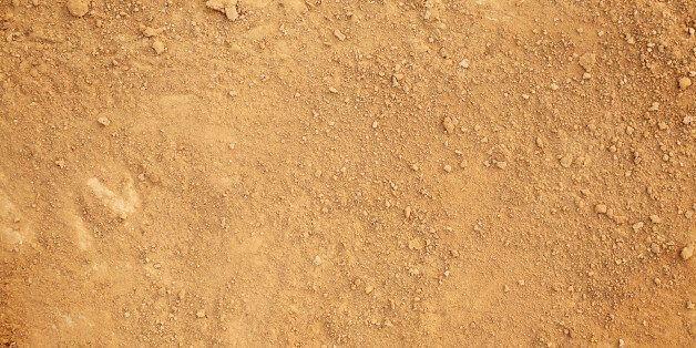 Photograph of tan colored dirt. Small clumps of dirt are sprinkled randomly over a layer of dry dirt...