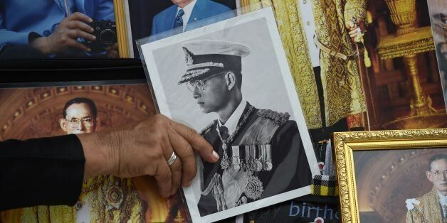 A woman holds an image of the late Thai King Bhumibol Adulyadej as mourners wait for his funeral to begin...
