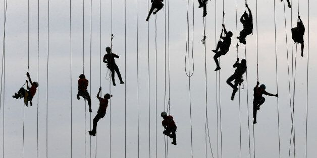 People climb after jumping off a bridge, which has a height of 30 meters, in Hortolandia, Brazil, October...