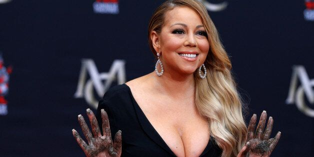 Singer Mariah Carey shows her hands after placing them in cement in the forecourt of the TCL Chinese...