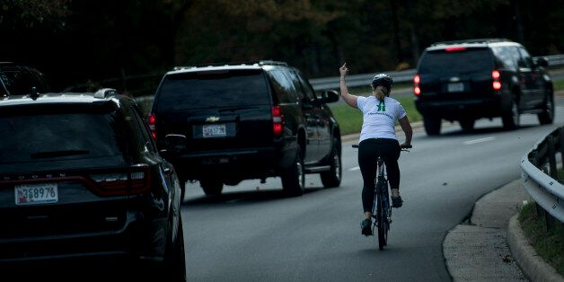 TOPSHOT - A woman on a bike gestures with her middle finger as a motorcade with US President Donald Trump...