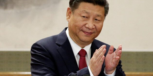 China's President Xi Jinping claps after his speech as he and other new Politburo Standing Committee...