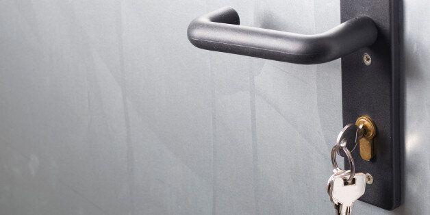 A door handle with lock and keys. The door is