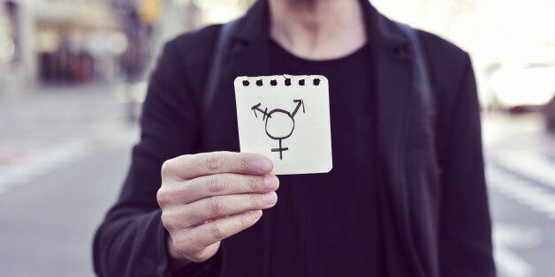 closeup of a young Caucasian man in the street showing a piece of paper with a transgender symbol drawn...