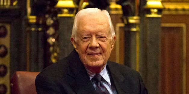 Former U.S. President Jimmy Carter sits after delivering a lecture on the eradication of the Guinea worm,...