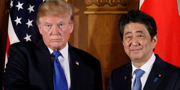 U.S. President Donald Trump and Japan's Prime Minister Shinzo Abe shake hands at the end of a news conference...