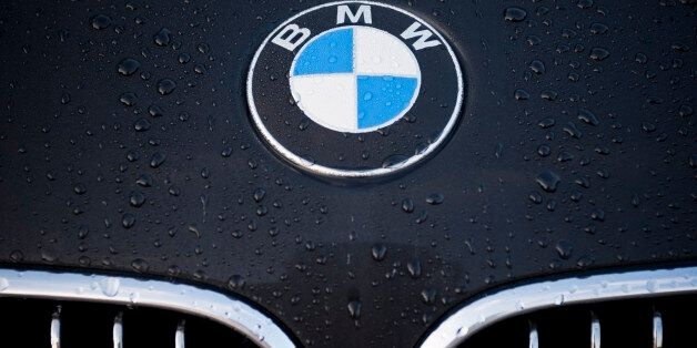 'Padua, Italy - July 6, 2011: Circle shape BMW logo and part of the front grill on a black car covered...