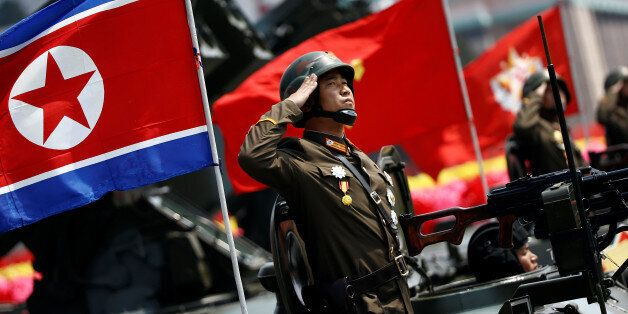 A soldier salutes from atop an armoured vehicle as it drives past the stand with North Korean leader...