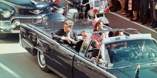 President and Mrs. John F. Kennedy smile at the crowds lining their motorcade route in Dallas, Texas,...