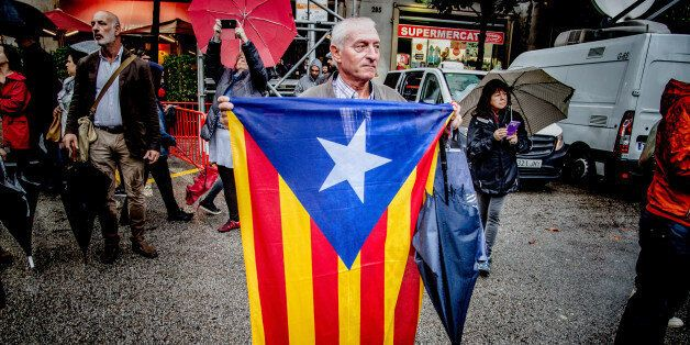 BARCELONA, CATALONIA, SPAIN - 2017/10/19: A man is seen while holding a flag of Catalonia front of the...