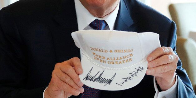U.S. President Donald Trump holds a hat he and Japan's Prime Minister Shinzo Abe signed,