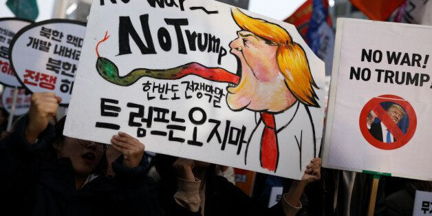 Demonstrators hold placards during a protest ahead of U.S. President Donald Trump's visit near the U.S....