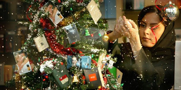An Iranian woman decorates a store front with Christmas decorations in Tehran December 23, 2003. Christmas,...