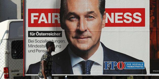 VIENNA, AUSTRIA - OCTOBER 14: A man of African origin walks past an election campaign billboard that...