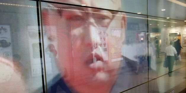 Passersby are reflected in a TV screen reporting news about North Korea's leader Kim Jong Un and their...