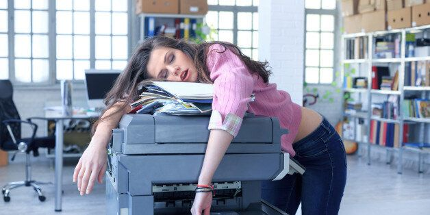 Tired young woman with messy hair sleeping on folders with documents and a copy machine, in the office....