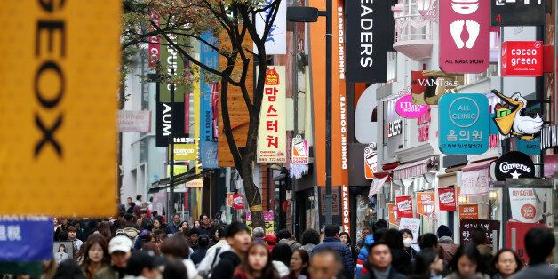 People walk past stores at the Myeongdong shopping district in Seoul, South Korea, on Monday, Oct. 31,...