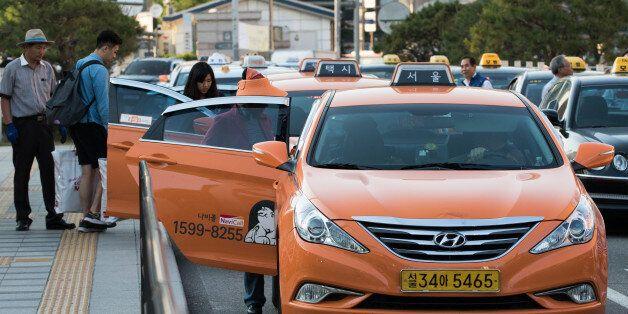 Passengers board taxis outside Seoul Station in Seoul, South Korea, on Monday, May 25, 2015. South Korea...