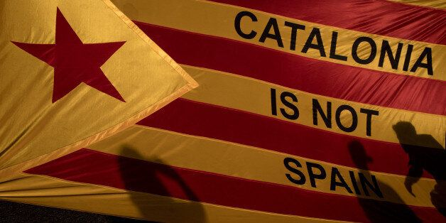 BARCELONA, SPAIN - OCTOBER 03: Protesters shadows are seen on a Catalan flag as thousands of citizens...