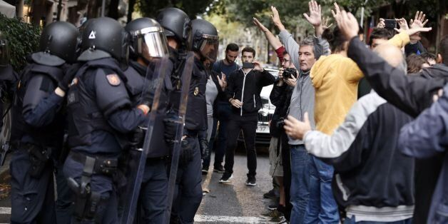 People raise their arms in front of Spanish police after the seizure of ballot boxes in a polling station...