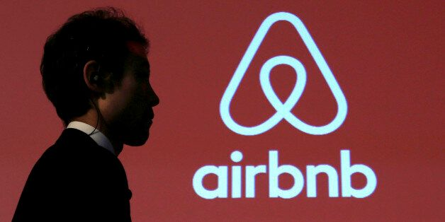 A man walks past a logo of Airbnb after a news conference in Tokyo, Japan, November 26, 2015. REUTERS/Yuya...