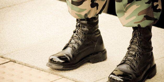 A solider in shiny boots stands at