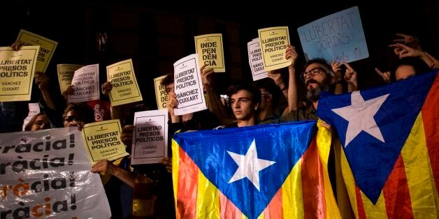 People hold Esteladas (Pro-independence Catalan flag) and papers reading in Catalan 'Freedom political...