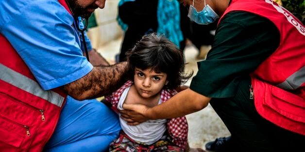 Members of the Kurdish Red Crescent check a displaced girl after she left with her father central Raqa...