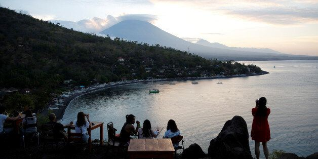 Tourists have a drink while watching the sunset behind Mount Agung, a volcano on the highest alert level,...