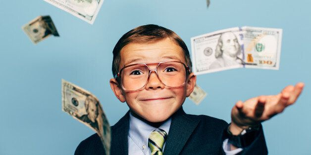 A young boy accountant wearing glasses catches U.S. currency while more falls from above. He is smiling...
