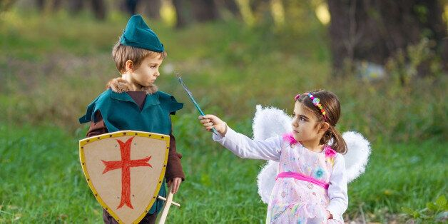 Cute little children dressed up as a fairy and a knight playing in a
