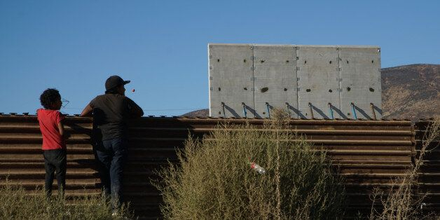 TIJUANA, MEXICO - OCTOBER 5: People watch prototype sections of a border wall between Mexico and the...