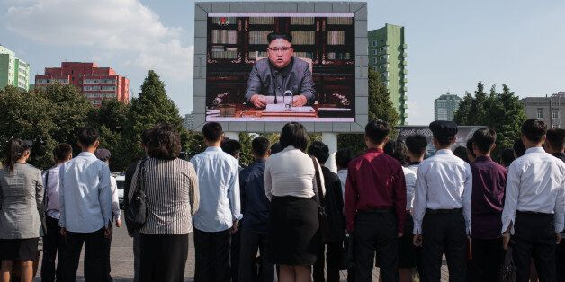TOPSHOT - Spectators listen to a television news brodcast of a statment by North Korean leader Kim Jong-Un,...