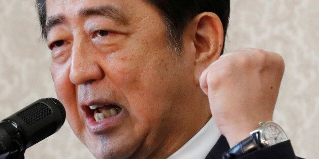 Japan's Prime Minister Shinzo Abe makes his fist as he speaks to his party's lawmakers at the party lawmakers'...