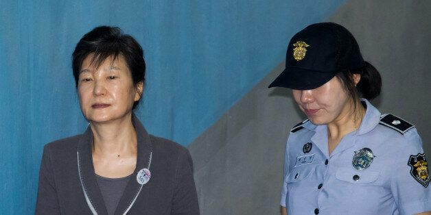 Park Geun-hye, former president of South Korea, left, is escorted by a prison officer as she arrives...
