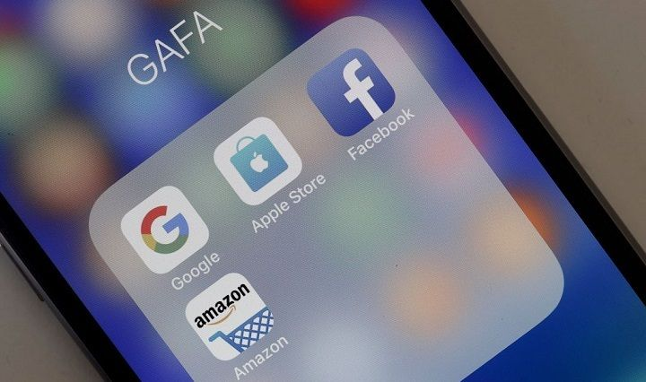 A photo illustration shows logos for Google, Apple, Facebook, and Amazon applications on the screen of an Apple iPhone.