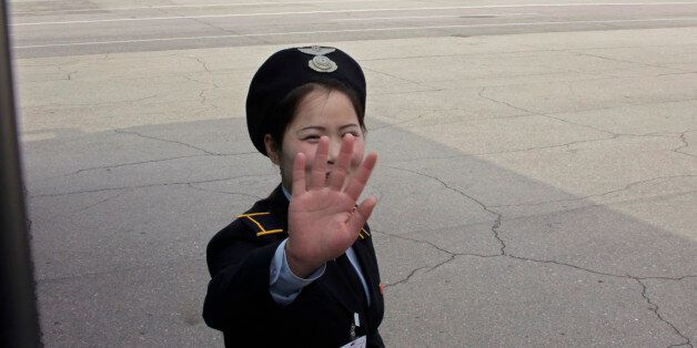 A ground staff of North Korean airliner Air Koryo thrusts a hand in front of her face at the airport...
