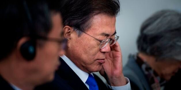South Korea's President Moon Jae-in listens to a statement before luncheon with US, Korean, and Japanese...