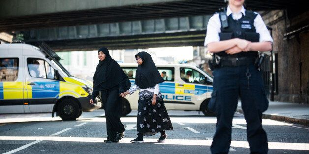 LONDON, UNITED KINGDOM - JUNE 19: A muslim woman and child hold hands and walk past police near the scene...