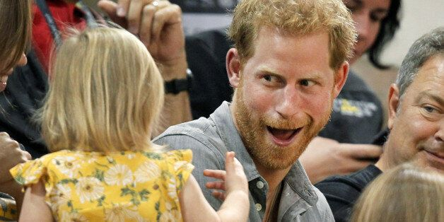 Britain's Prince Harry, patron of the Invictus Games Foundation, shares popcorn with a child while attending...