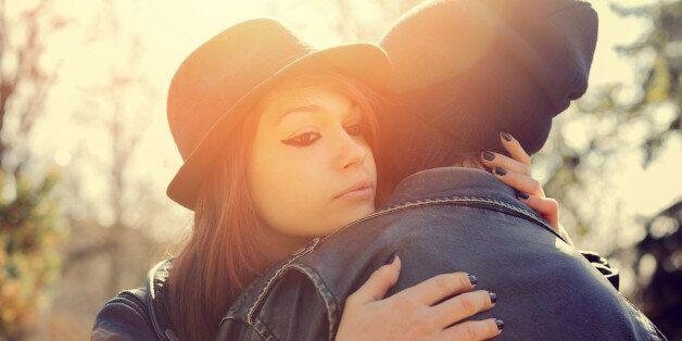Teenage girl embracing a boy in the
