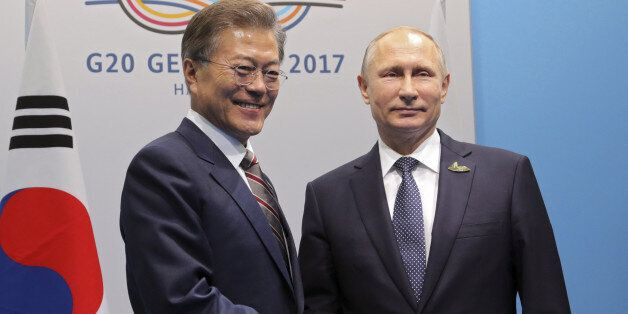 Russia's President Vladimir Putin (R) shakes hands with South Korea's President Moon Jae-in during a...