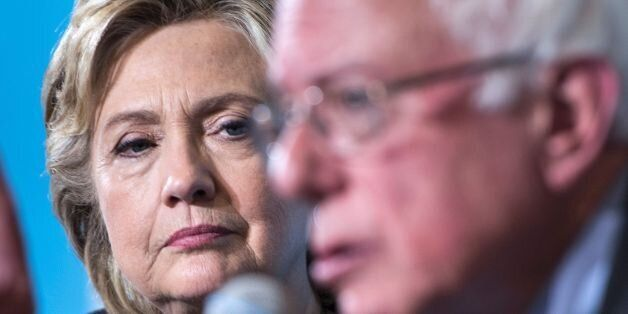 Democratic presidential nominee Hillary Clinton listens as Senator Bernie Sanders (I-VT) speaks during...