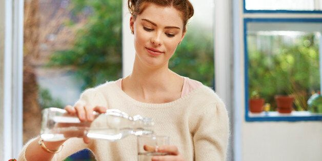 Shot of a young woman pouring a glass of water at